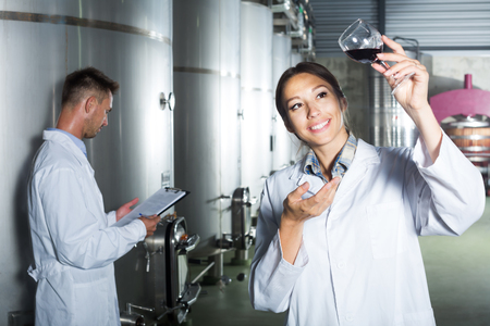 Portrait of glad woman in uniform looking at wine sample in glass on winery manufactory Stock Photo