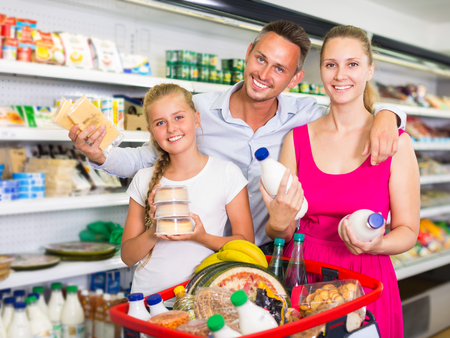 Portrait of family which is choosing milk in supermarket. Imagens - 122066596