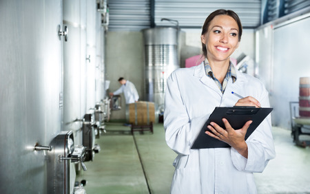 Young cheerful woman wearing a coat taking notes in secondary fermenting section at wine factory