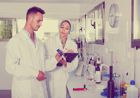 Two diligent positive researchers in white coat checking wine acidity and sugar saturation in chemical laboratory