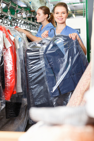 Confident diligent positive smiling woman worker of dry cleaner showing clean clothes in plastic garment bag Banco de Imagens