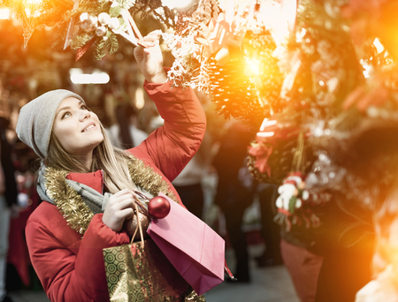 Girl choosing Christmas gifts outdoor on street market