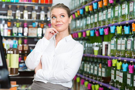 Portrait of girl thinking about buying new fragrance in perfume shop