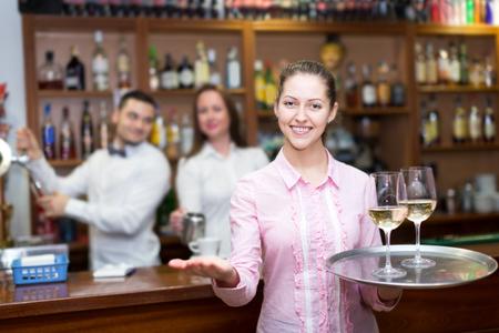 Heureuse serveuse tenant un plateau avec des lunettes, barmans à distance Banque d'images