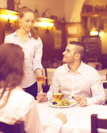 Spouses eating out in a rural restaurant while young waitress is bringing them the food that they had ordered