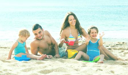Felices padres jóvenes con dos niños jugando con arena en la playa Foto de archivo