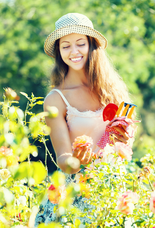 Portrait of smiling young woman in roses plant at garden