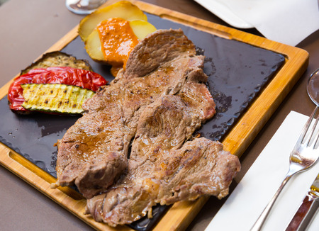 Appetizing grilled beef steak with baked potatoes topping with romesco sauce and vegetables