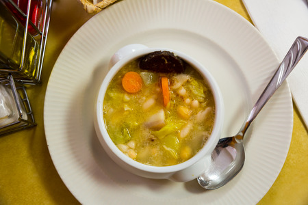 Catalan soup of bean with boiled carrots, potatoes and blood sausage served in bowl