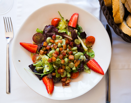 Top view of salad with candied beans, bacon marinated in soy-honey sauce, tomatoes, fruits and greens