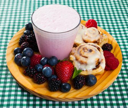 Homemade cinnamon buns with milkshake and fresh berries