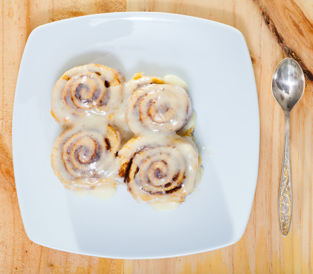 Top view of soft and fluffy cinnamon rolls topped with sugar glaze on white plate Stock Photo