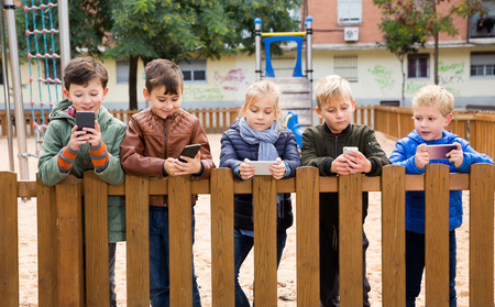 Group of preteen children standing near wooden fence on playground, addicted in their phones