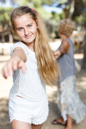 Portrait of  teenage  girl pulling hand and hold grandmother on hand in green park