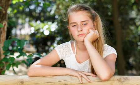 Portrait of upset  teenage  girl standing near fence  in green park at summer day