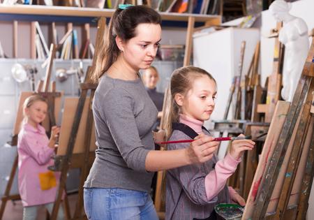 Smiling female teacher assisting student during painting class at studio 版權商用圖片