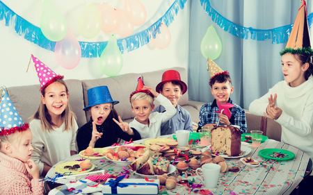 Smiling kids having good time during friend's birthday party