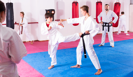 serious young children working in pair mastering new karate moves during group class with male coach