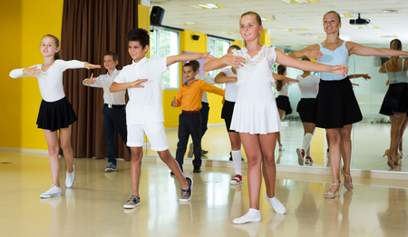 Boys and girls dancing in class with young woman instructor and smiling. Focus on boy