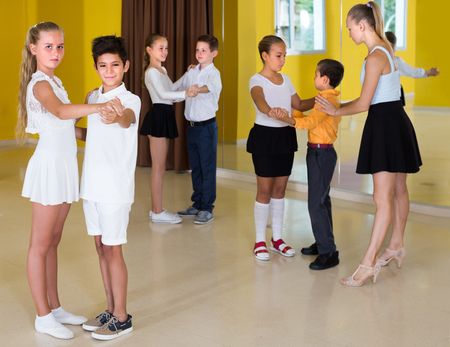 Positive children are dancing waltz in class.