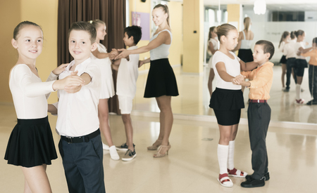 Positive active young children  enjoying of partner dance in class