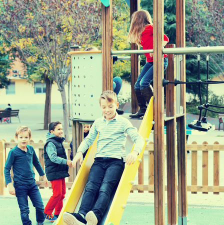 Smiling  glad children in school age sliding down together on playgrounds construction outdoors. Focus on left boy Reklamní fotografie