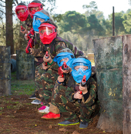 Group of lucky kids in camouflages and masks playing paintball aiming with gun in shootout outdoors Фото со стока - 122243443