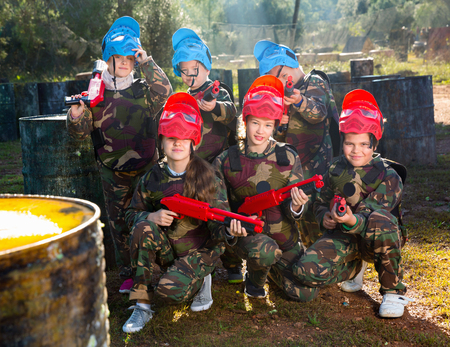 Friendly positive smiling group of children paintball players in camouflage posing with guns on paintball playing field outdoors Фото со стока - 122252436