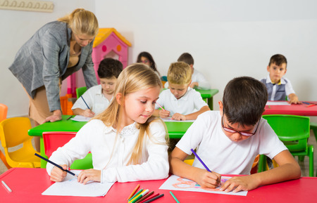 Portrait of children discussing theirs drawings during lesson in school