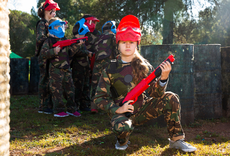sportive girl paintball player in camouflage standing with gun before playing outdoors