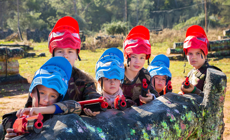 Portrait of little kids paintball players wearing uniform and holding guns ready for playing outdoor