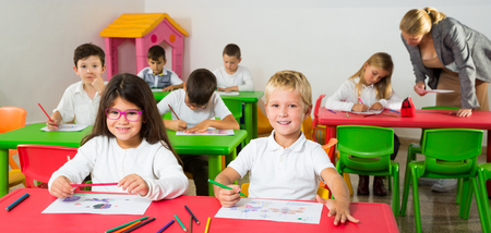 Portrait of happy pupils working in classroom at elementary school Stok Fotoğraf - 122252654