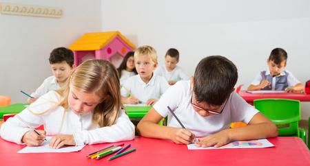 Portrait of diligent focused pupils studying in classroom at elementary school 版權商用圖片