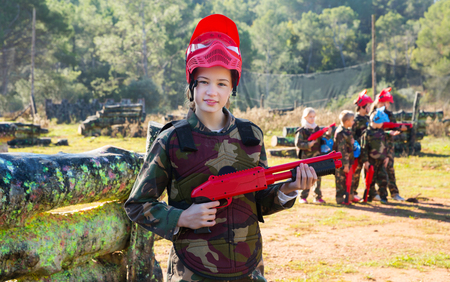 active tweenage girl paintball player in camouflage standing with gun before playing outdoors Фото со стока