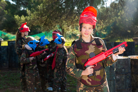 portrait of cheerful tweenage girl paintball player in camouflage standing with gun before playing outdoors