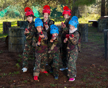 Portrait of positive kids paintball players wearing uniform and holding guns ready for playing outdoor