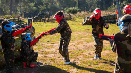 Teams of active happyt kids facing on battlefield in outdoor paintball arena