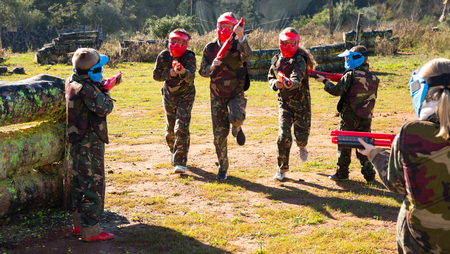 Two opposing teams of modern kids shooting on paintball playing field outdoors Фото со стока - 122252812