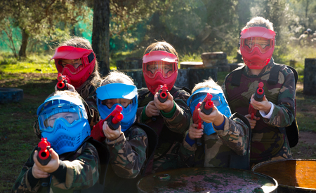 Boys and girls paintball players aiming and shooting with guns at opposing team outdoors