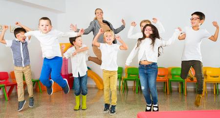 Gruppo di bambini allegri felici con la loro insegnante che salta insieme nell'aula scolastica