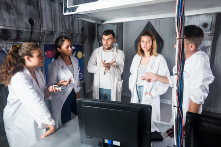 Adults are solving quests to get out of escape room stylized like laboratory.