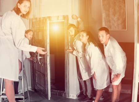 Group of surprised positive adults wearing lab coats finding entrance to another quest room Banque d'images
