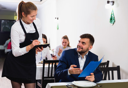 Woman waiter is taking order from client in restaurante indoor.