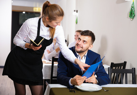 Welcoming female waiter is taking order from businessman in restaurante indoor. Banco de Imagens