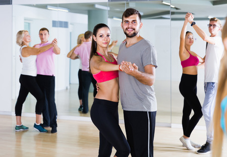 Dancing positive ukrainian couples learning salsa at dance class