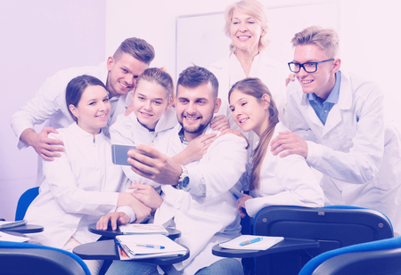Adult students of medical faculty with female teacher making selfie indoors