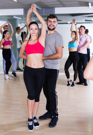 Group of positive smiling young dancing salsa in club Imagens