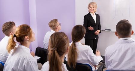Elegante insegnante femminile che tiene lezioni agli studenti all'auditorium