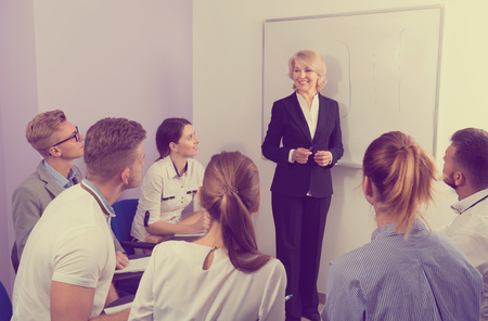 Glad pleasant female speaker giving presentation for smiling students in lecture hall 版權商用圖片