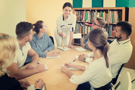 Nette Studenten mit Lehrerin, die im Klassenzimmer studiert